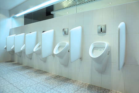 line of six white porcelain urinals in clean, light public toilets