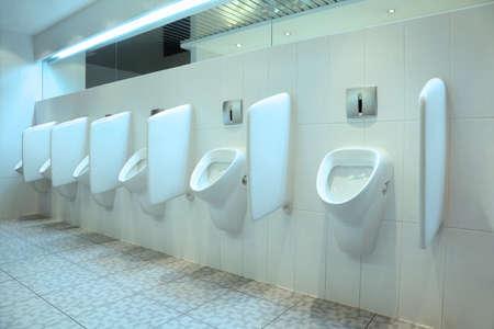 line of six white porcelain urinals in clean, light public toilets