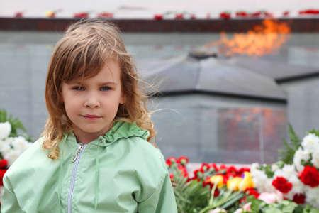 blotter: beautiful little girl stands near memorial, eternal flame, flowers Stock Photo