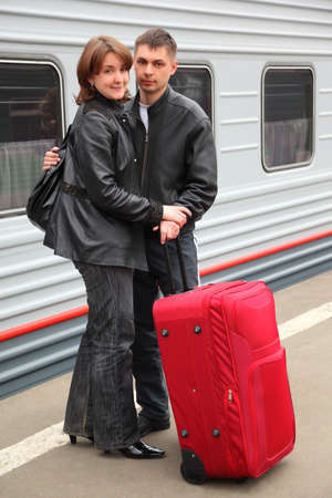 husband and wife with big red bag stand on perron near train photo