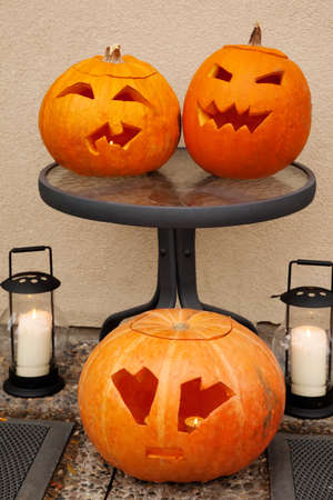 little table: Three pumpkins of Halloween. Two lie on glass little table. One lies on floor