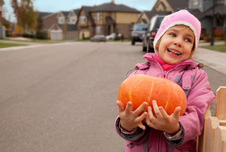 Smiling girl goes on road and bears pumpkin in hands photo