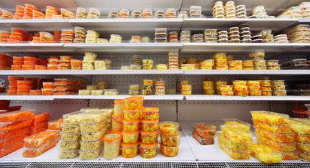 大型店の棚にプラスチック容器で異なるサラダ