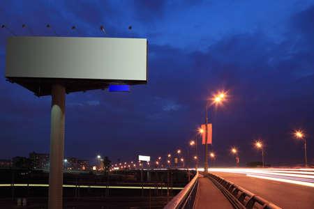 Big gray billboard with illumination at night, road, bridge and lanterns 스톡 콘텐츠
