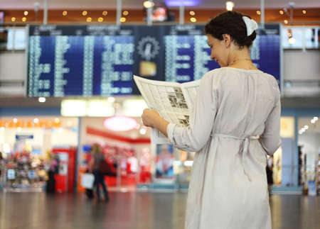 beautiful young woman standing in hall of airport and reading newspaper photo