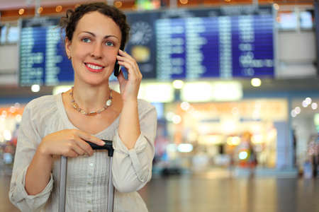 beautiful young woman sitting on their luggage in hall of airport and talking by mobile phone photo