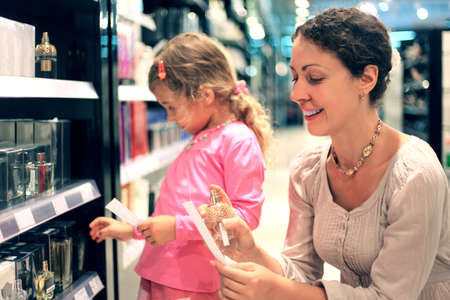 香水ショップで香水を選ぶ若い母親と幼い娘、母親に焦点を当てる