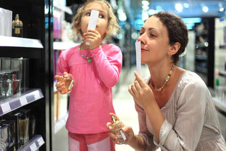 young mother and little daughter choose perfume in perfume shop, focus on mother hand