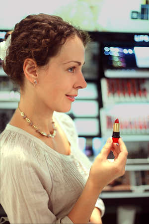 beautiful young woman chooses red lipstick in store, holding lipstick photo