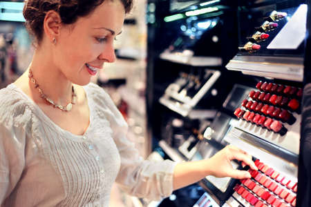 beautiful young woman chooses lipstick in store. bid assortiment photo