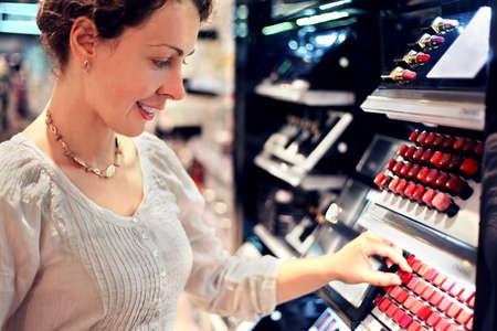bid: joven y bella mujer elige el l�piz labial en la tienda. oferta assortiment