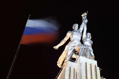 Trabajador y monumento granja colectiva en Moscú en la noche, el martillo y la hoz, bandera rusa