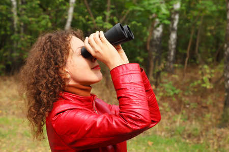 beautiful young woman dressed in red leather jacket, looks through binoculars outside photo
