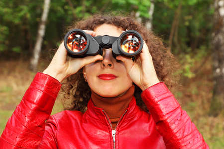 face of beautiful young woman dressed in red jacket looks through binoculars outside photo