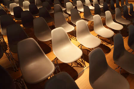 several rows of white plastic chairs with metal legs on yellow floor