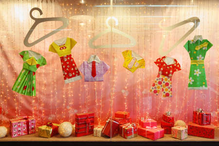 holiday display: Beautiful pink storefront with gifts and colored paper clothing