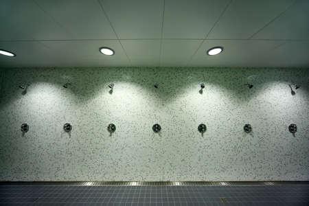 tap room: big, light, empty public shower room, green tile on walls, gray floor