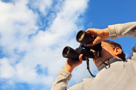 Little cute boy with binoculars outdoor; blue sky with white clouds photo