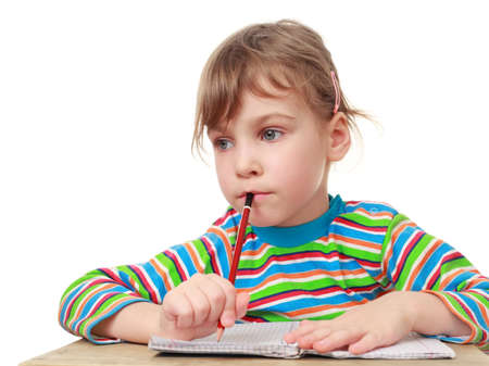 thinks: beautiful little girl thinks, pencil in hand and notebook on table Stock Photo
