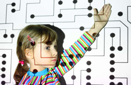 little girl in striped shirts shows on black circle on circuit, board, projector photo