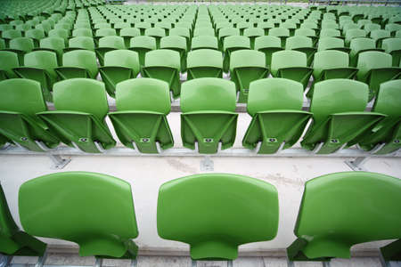 catena: Rows of folded, green, plastic seats in very big, empty stadium. Focus on front seats