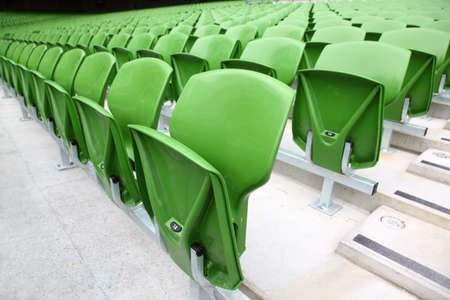 grandstand: Rows of folded, green, plastic seats in very big, empty stadium. Focus on front seats