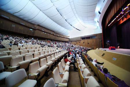 exhibition crowd: molte persone sono seduti in poltrone in grande sala per conferenze; ??tavola rosso sulla scena