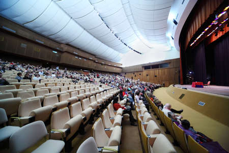 many people are sitting in easy chairs in big conference hall; red table on scene