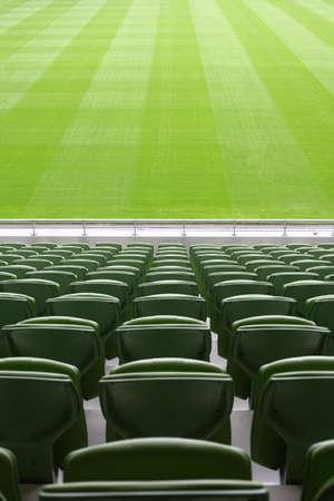 catena: Rows of folded, green, plastic seats in very big, empty stadium