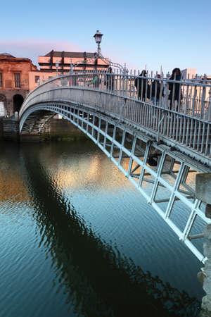 アイルランド、ダブリンのリフィー川のハーペニー橋に行く人