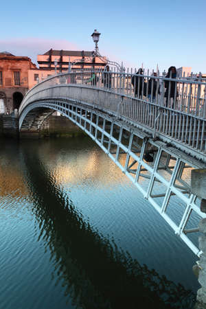 People going on Hapenny Bridge, Liffey River in Dublin, Ireland Editorial