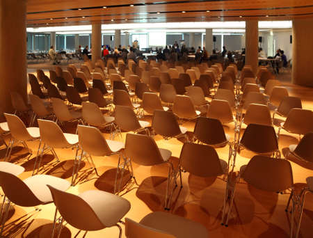 several rows of white plastic chairs; people in light conference room photo