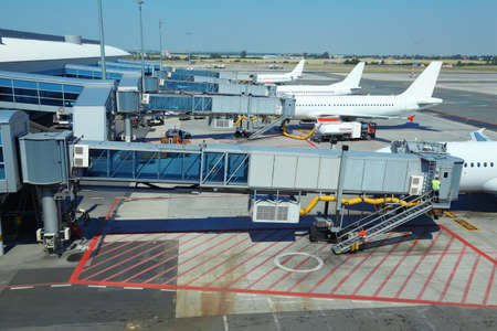 few: few airliners parked at airport. boarding passengers. service technician