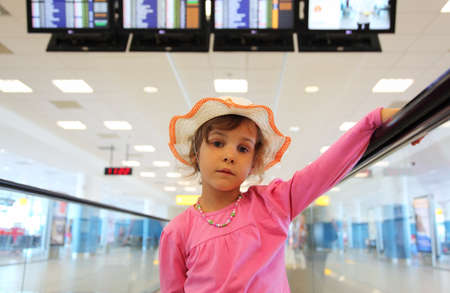 beautiful little girl in hat and pink blouse rides on escalator, schedule on displays photo