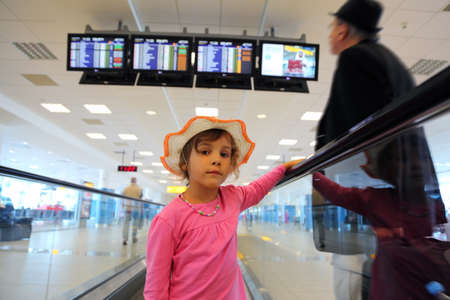 beautiful little girl in hat and pink blouse rides on escalator. old man in black wear. schedule on displays Stock Photo - 17795657