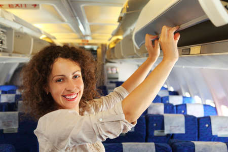 passenger compartment: young beautiful woman on airplane adds baggage, rows of blue seats Stock Photo