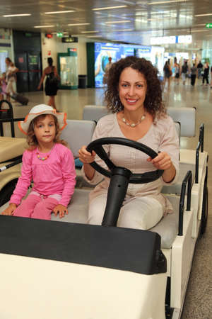 young mother and little daughter riding on electric car in airport photo