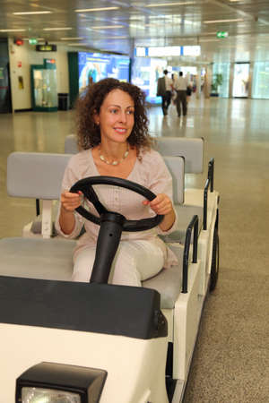 young beautiful woman in white wear riding on electric car in airport photo