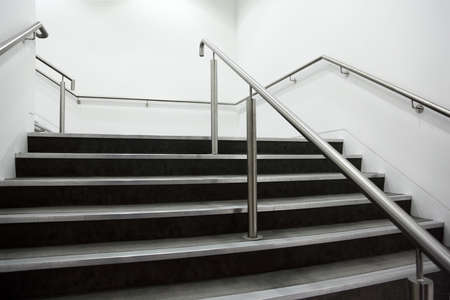 cleanly: wide staircase with chrome handrails and gray steps, white walls