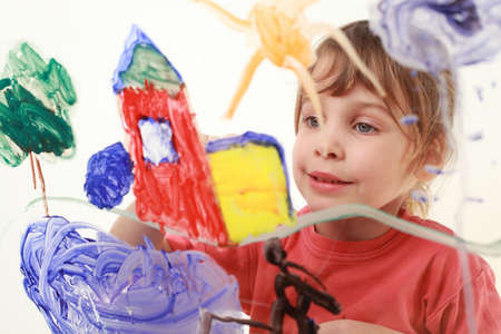 intent: beautiful little girl in red t-shirt paints on glass, house, tree, sun