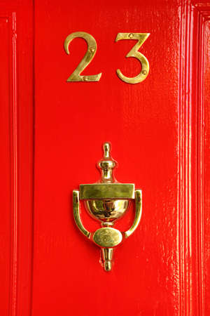 number lock: golden sign on red wooden door; 23 and cup; reflection in cup
