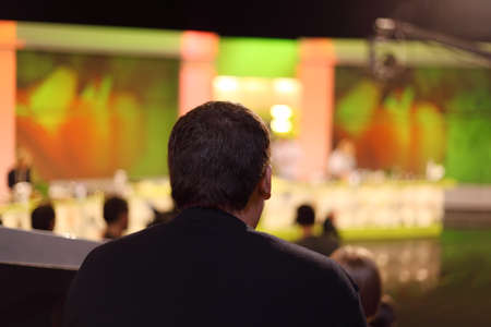 onlooker: man sits in television studio and watches show on stage, behind Stock Photo