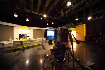professional black video camera in television studio, light scene Editoriali