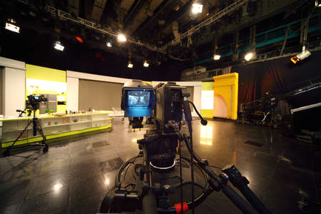 professional black video camera in television studio, light scene Editorial