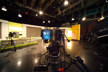 professional black video camera in television studio, light scene Editoriali