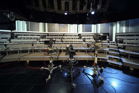tv set: three professional black video cameras in television studio, seats for audience
