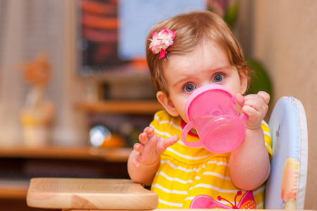 baby on chair: little girl sitting at the table. drink water