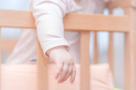 small child standing in a crib in clothes
