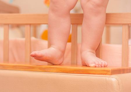 cot: small child legs near the cot. Stock Photo