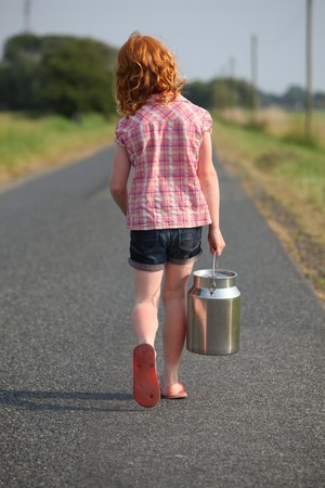 Red-haired girl with milk can on her way to the farm